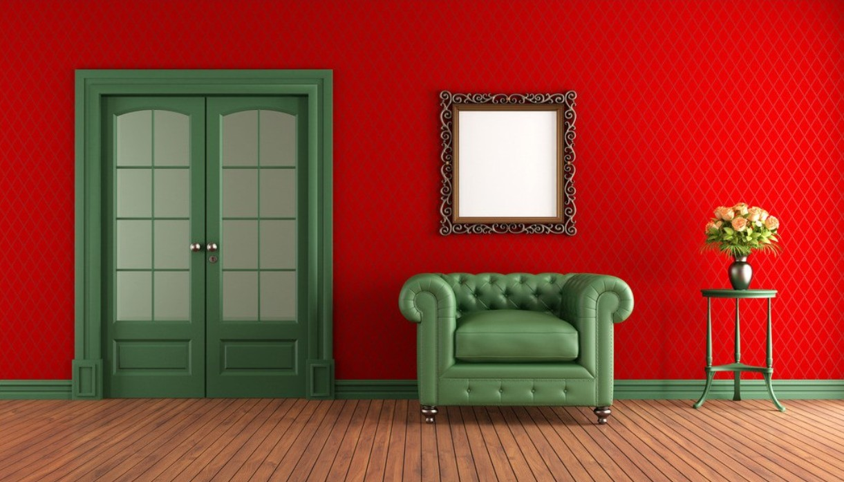 room with red walls and green sofa with mirror on the wall