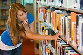 woman looking for book on bookshelf