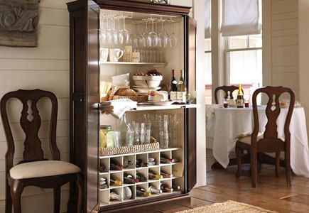dining room cupboard with wineglasses, table with tablecloth in background