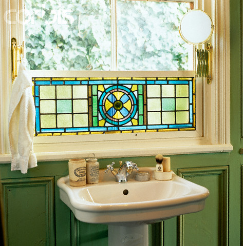 green bathroom with stained-glass window